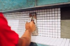 Die Arbeitskraft, die keramische Musterfliesen des Mosaiks auf Badezimmer planiert, duschen Bereich lizenzfreies stockbild