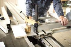 Die Arbeitskraft, die Silikon glueCloseup Prozess der Tischlerarbeitskraft mit Rundschreiben verwendet, sah Maschine am Kreuzauss Lizenzfreies Stockfoto