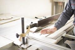Die Arbeitskraft, die Silikon glueCloseup Prozess der Tischlerarbeitskraft mit Rundschreiben verwendet, sah Maschine am Kreuzauss Stockbild