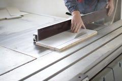 Die Arbeitskraft, die Silikon glueCloseup Prozess der Tischlerarbeitskraft mit Rundschreiben verwendet, sah Maschine am Kreuzauss Stockfoto