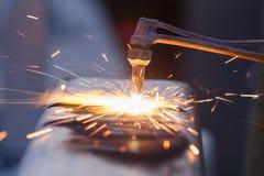 Die Arbeitskraft, die Stahlrohr unter Verwendung der Metallfackel schneidet und installieren Straßenrand Lizenzfreies Stockbild