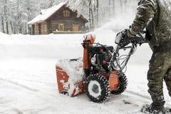 Die Arbeitskraft entfernt den Schnee mit einem Pflug Landschaft im Winter, Ru Lizenzfreies Stockfoto