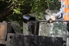 Die Arbeitskraft gießt heißes Bitumen in den Eimer Stockfotos