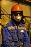 Die Arbeitskraft im Overall und in einem Respirator lizenzfreies stockbild