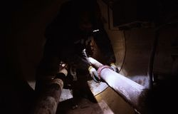 Die Arbeitskraft im Tunnel repariert die Rohrleitung Reparieren Sie Arbeit Stockfotos