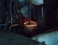 Die Arbeitskraft macht die Verhärtung der Wärmebehandlung des Metallgangs auf einer speziellen Maschine, Nahaufnahme, die Verhärt lizenzfreie stockbilder