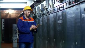 Die Arbeitskraft notiert die Lesungen der Meter in dem Kraftwerk Ein Mann in einem Sturzhelm und in einer Arbeitsrobe stock footage