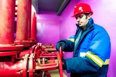 Die Arbeitskraft schließt eine Klinke der industriellen Rohrleitung lizenzfreie stockfotos