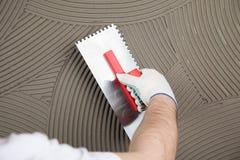Die Arbeitskraft trägt Kleber für eine Fliese auf einer Wand auf Lizenzfreie Stockbilder