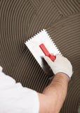 Die Arbeitskraft trägt Kleber für eine Fliese auf einer Wand auf Stockfotografie