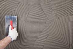 Die Arbeitskraft trägt Kleber für eine Fliese auf einer Wand auf Lizenzfreies Stockfoto