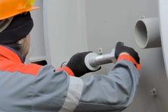 Die Arbeitskraft verdreht die Nüsse Arbeitskraft der Anlage Arbeitskraft in einem Sturzhelm lizenzfreies stockfoto