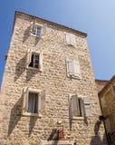 Die Architektur des alten Montenegros: Hölzerne Fensterläden auf einer Steinwand des Hauses Stockfotografie