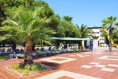 Die Architektur des türkischen Hotels mit den Sonnenruhesesseln, Palmen und Leuten, die im Sommer sich entspannen lizenzfreie stockfotos