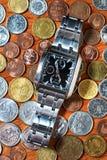 Die Armbanduhr der Männer auf Metallmünzen Lizenzfreie Stockbilder