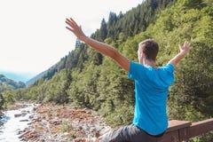 Die Arme des Mannes hoben auf eine Br?cke an, die einen Fluss kreuzt, der durch Berge umgeben wurde lizenzfreie stockfotografie