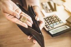 Die Armehand, die Münze nach Zahltag hält, Konkurs brach stockbild