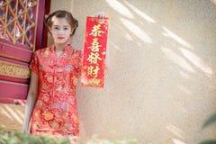 Die Asiatin auf Chinesisch kleiden das Halten des Distichons 'lukrativ' (C Lizenzfreie Stockbilder