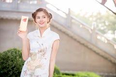 Die Asiatin auf Chinesisch kleiden das Halten des Distichons 'lukrativ' (C Lizenzfreie Stockfotografie