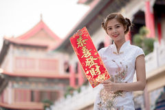 Die Asiatin auf Chinesisch kleiden das Halten des Distichons 'lukrativ' (C Stockbilder