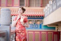 Die Asiatin auf Chinesisch kleiden das Halten des Distichons 'lukrativ' (C Stockbild
