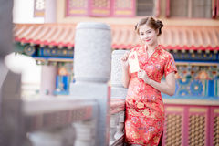 Die Asiatin auf Chinesisch kleiden das Halten des Distichons 'lukrativ' (C Stockfoto