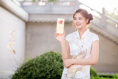 Die Asiatin auf Chinesisch kleiden das Halten des Distichons 'lukrativ' (C Stockfotos