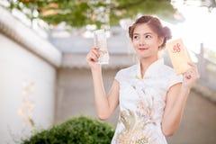 Die Asiatin auf Chinesisch kleiden das Halten des Distichons 'lukrativ' (C Lizenzfreie Stockfotos