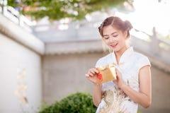 Die Asiatin auf Chinesisch kleiden das Halten des Distichons 'lukrativ' (C Lizenzfreies Stockbild