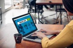 Die Asiatin, die Laptop-Computer verwendet, tun on-line-Netz der Suchtendenzen 2019 auf hölzerner Tabelle am Caférestaurant Digit stockbilder