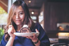 Die Asiatin, die Schokoladenkuchenrolle und -Schlagsahne halten und die Gabel mit dem Fühlen glücklich und genießen, im modernen  stockfotografie