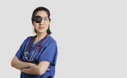Die asiatische Ärztin, die eine Augenklappe oben schaut mit den Armen trägt, kreuzte über grauem Hintergrund Stockbild