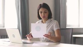 Die asiatische Geschäftsfrau, die mit Laptopdokumenten arbeitet, schreiben Anmerkungen in Büro stock video