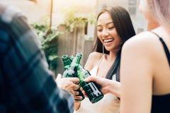 Die asiatische Gruppe, die das Rösten genießt, trinkt Partei mit klirrendem Bier BO lizenzfreie stockbilder