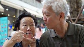 Die asiatischen älteren Videopaare, die eine Eiscreme essen und ziehen sich abstrakte ewige Liebe ein