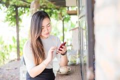 Die asiatischen Frauen des Geschäfts, die am intelligenten Telefon im modernen coffe simsen, kaufen stockbild