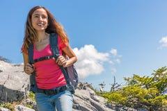 Die asiatischen Frauen wandern, die mit dem Wandern der Pole und dem Wandern des lächelnden glücklichen Freiens des Rucksacks in  Stockfotos