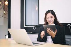 Die asiatischen Geschäftsfrauen, die Tablette für das Arbeiten im Büro verwenden, entspannen sich t lizenzfreies stockfoto
