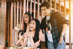 Die asiatischen Gruppenleute, die am Restaurant sich treffen mit, genießen, Berufskleidung zu lachen stockfotos
