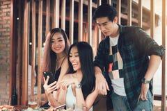 Die asiatischen Gruppenleute, die am Restaurant sich treffen mit, genießen, Berufskleidung zu lachen stockfoto