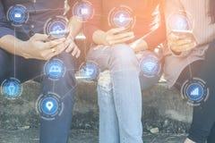 Die asiatischen jugendlich Freunde, die mit intelligentem Telefon schließen sitzen in der Hand, an Social Media an Technologiever lizenzfreie stockfotografie