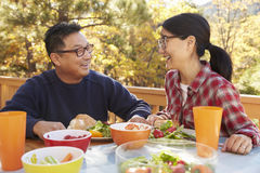 Die asiatischen Paare, die an einem Tisch draußen zu Mittag essen, lachen zusammen Lizenzfreie Stockfotografie