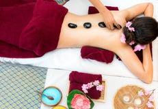 Die Asien-Schönheitsfrau, die sich auf Massagebett mit traditionellen heißen Steinen entlang dem Dorn in der thailändischen Badek stockfotografie