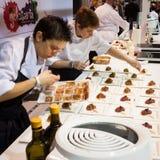 Die Assistenten des Chefs, die bei Golosaria 2013 in Mailand, Italien arbeiten lizenzfreie stockfotos