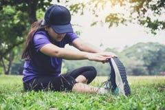 Die Athletenfrau, die etwas Ausdehnen tut, übt Aufwärmen vor Lauf aus stockfotos