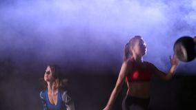Die athletischen sexy Frauen, Eignung tuend trainiert mit Gewichtungen, nachts, im hellen Rauche, Nebel, im Licht eines stobascop stock video