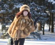 Die attraktive Frau in einem Fuchspelzmantel wird im Winter fotografiert Stockbilder