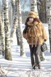 Die attraktive Frau in einem Fuchspelzmantel wird im Winter fotografiert Stockfotografie