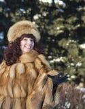 Die attraktive Frau in einem Fuchspelzmantel wird im Winter fotografiert Lizenzfreie Stockfotografie