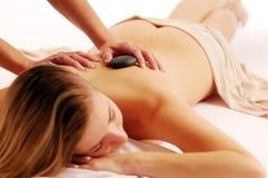 Die attraktive Frau während des masage mit Steinen stockbild